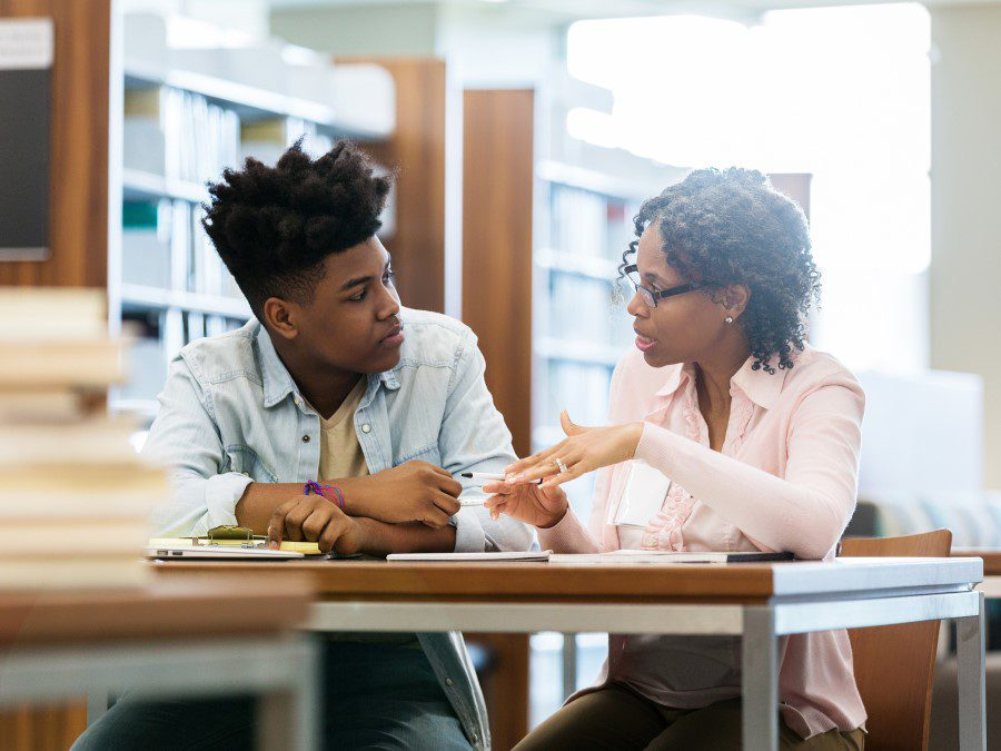 A teacher and a student of color, sitting and talking in a library